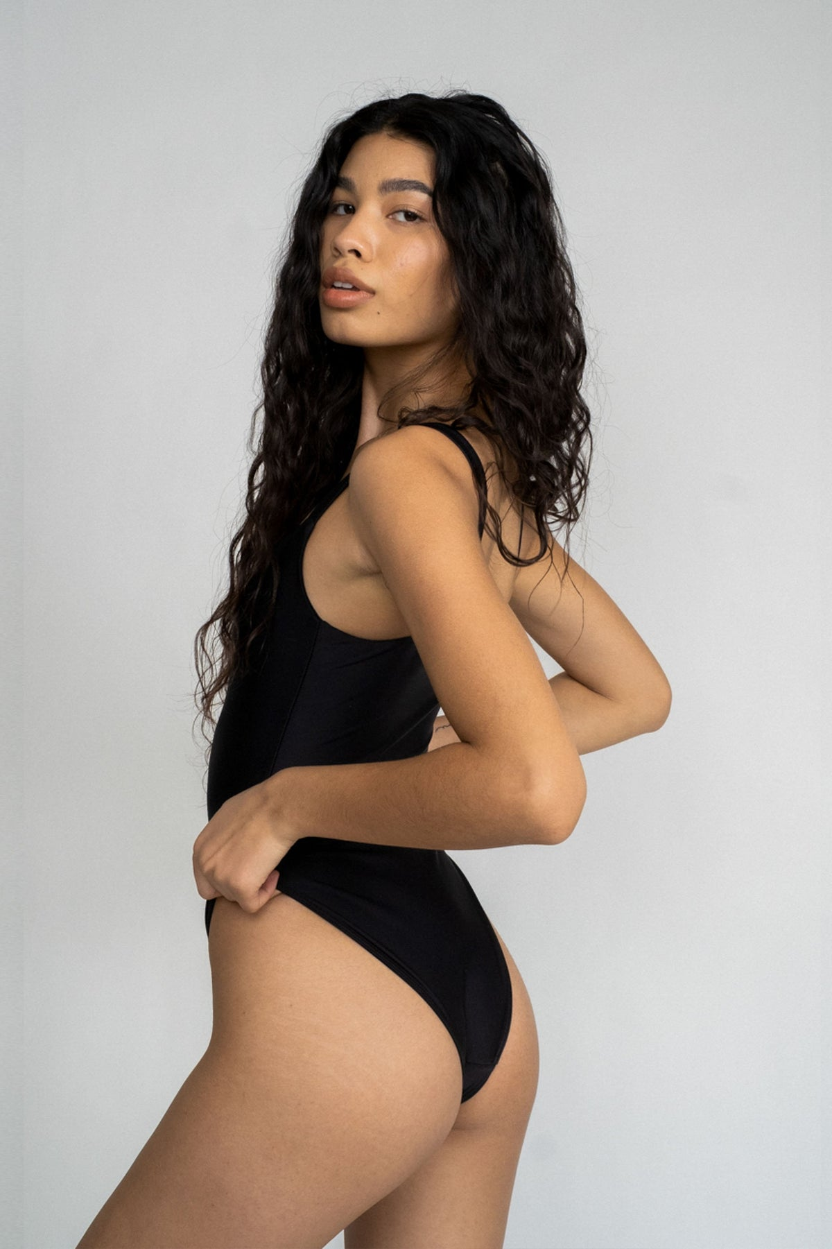 The back of a woman looking over her shoulder wearing a black one piece swimsuit with a straight neckline.