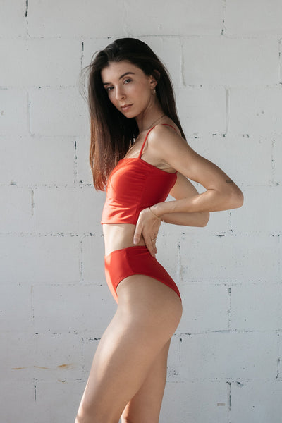 The side of a woman standing in front of a white brick wall wearing bright red high waisted bikini bottoms with a matching bright red tankini top.