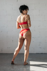 A woman standing and looking over her shoulder wearing high cut red bikini bottoms and a red bikini top with spaghetti straps.