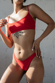 A close up of a woman with one hand on her hip wearing red high cut bikini bottoms and a red bikini top with a scoop neckline and spaghetti straps.