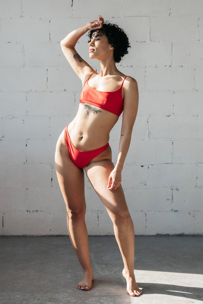 A woman standing in front of a white wall with one hand on her head blocking the sun wearing bright red high cut bikini bottoms and a matching bright red bikini top with a scoop neckline.