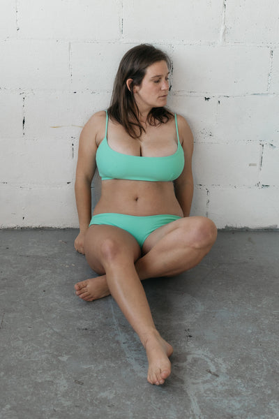 A woman sitting against a white wall with one leg crossed over another wearing bright turquoise high cut bikini bottoms and a bright turquoise bikini top with spaghetti straps and a scoop neckline.
