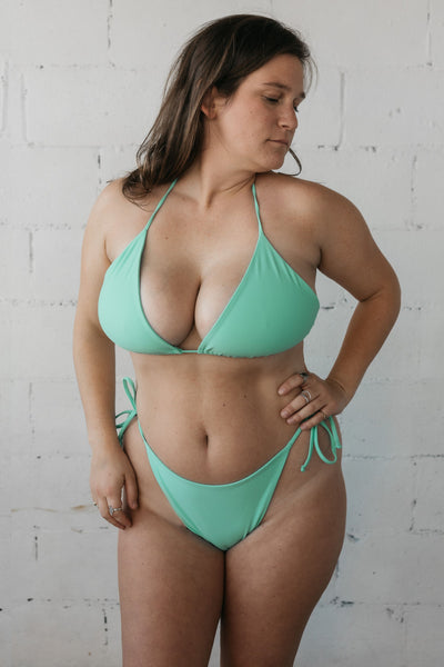 A woman standing looking down over her shoulder wearing turquoise triangle bikini bottoms with adjustable strings and a matching turquoise triangle string bikini top.