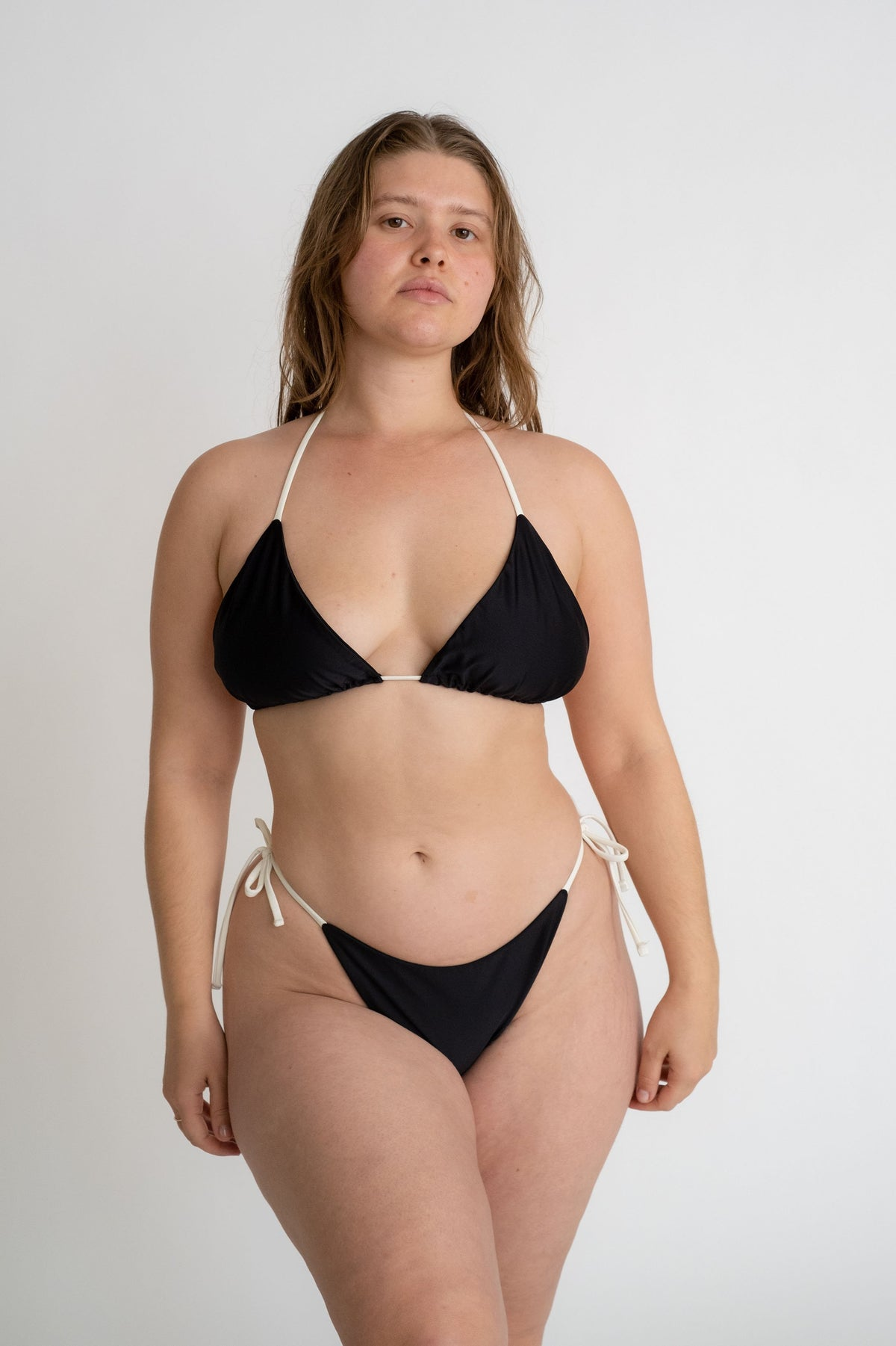 A woman standing with her arms relaxed by her sides wearing a black triangle bikini top with adjustable white straps and black triangle bikini bottoms with white strings.