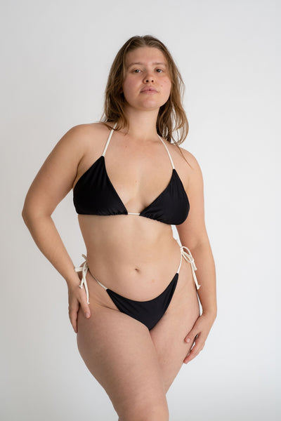 A woman standing with one hand on her hip wearing black triangle bikini bottoms with white string ties and a matching black triangle bikini top with adjustable white strings.