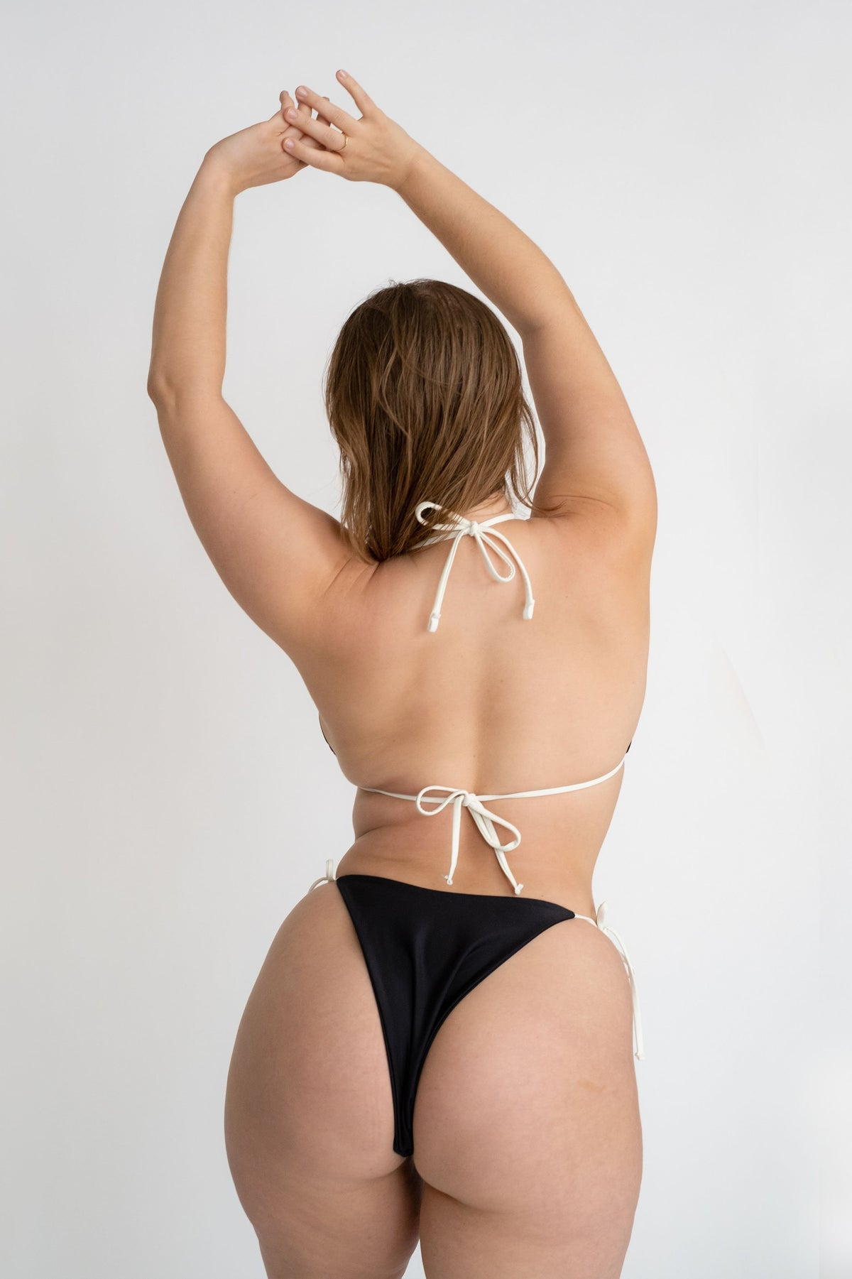 The back of a woman leaning to the side with her arms stretched above her head wearing a black triangle bikini top with adjustable white straps and black triangle bikini bottoms with white strings.