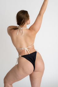 The back of a woman standing with one leg bent and one arm straight above her head wearing a black triangle bikini top with adjustable white straps and black triangle bikini bottoms with white strings.
