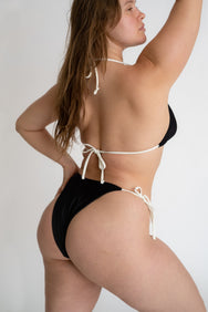 The back of a woman standing with her hand on her hip wearing a black triangle bikini top with adjustable white straps and black triangle bikini bottoms with white strings.