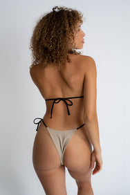 The back of a woman standing looking to the side wearing nude triangle bikini bottoms with adjustable black strings and a matching nude triangle bikini top with adjustable black straps.