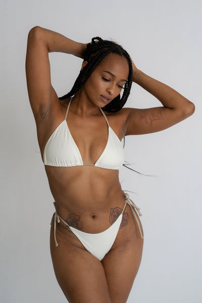 A woman looking down with her arms folded above her wearing white triangle bikini bottoms with adjustable nude string ties and a matching white bikini top with nude string ties.
