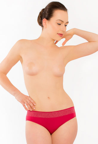 Model wears silicone stick on nipple covers with red briefs