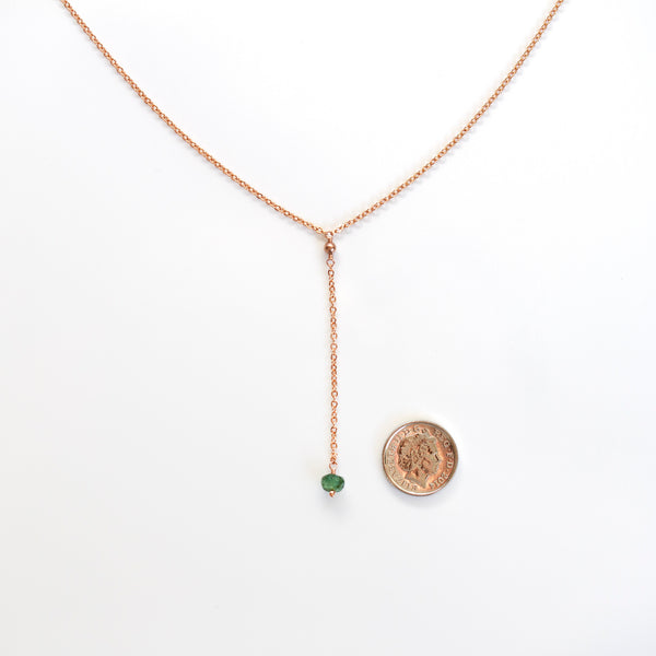 rose gold y necklace emerald next to 5p coin