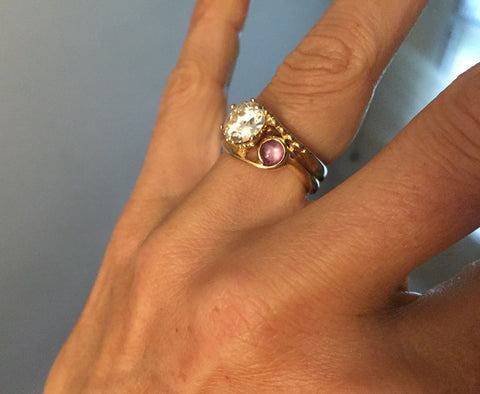 Two Stone European Cut Diamond and Star Ruby Yellow Gold Engagement Ring on Joanna Rubini's hand, ring by Rubini Jewelers