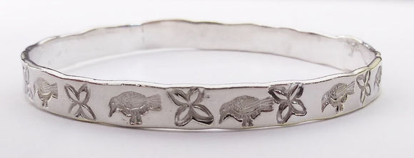 This delightful bangle is silver plated brass with a bird and flower pattern stamped into it around the entire bracelet.