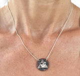 Silver Aether Symbol and Rowing Blade on Copper Disc Necklace by Rubini Jewelers, shown on woman's neck