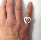 Crossed oars in heart ring shown on a finger.