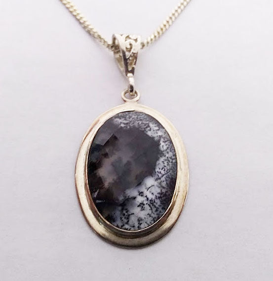 This beautiful faceted detritic agate stone has a very unique interesting look. It is bezel set in sterling silver with a wide filigree bail great for thick chains.