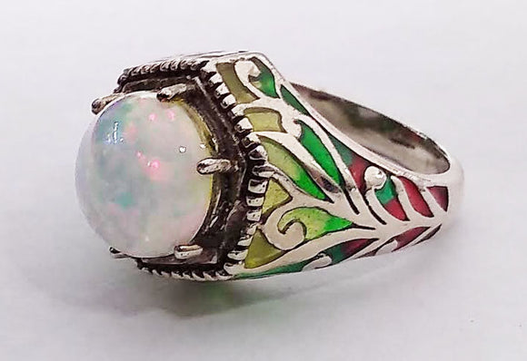 This sterling silver antique style ring has beautiful patterns in red, yellow, and green patterns of enamel. The 9.5mm faux opal has bright tones of red, pink, and blue.  Size 5 3/4.