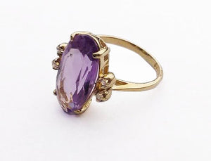 A lovely oval shaped faceted pale amethyst set in 14K yellow gold flanked by four melee diamonds.