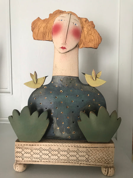 Girl with ginger hair and birds on stand
