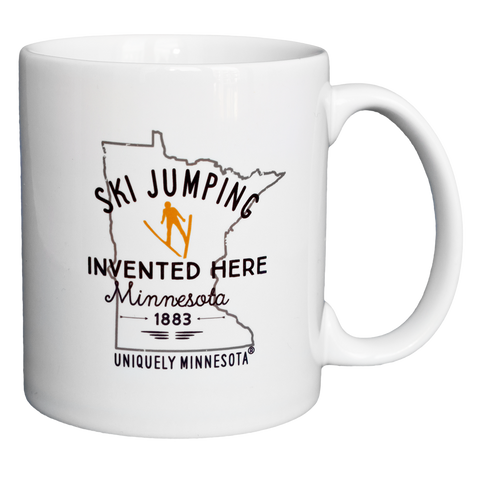 Uniquely Minnesota Ski Jumping invented in MN logo with golden skier icon 11 oz. white ceramic coffee mug.
