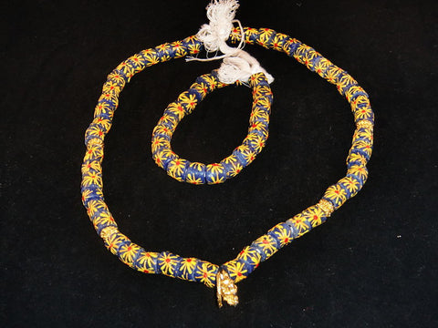 "Blue with hand-painted multi-colored starburst pattern & golden accents; on string / tie-on; neck beads approx. 25"" long; wrist beads approx. 10 1/2"" long."