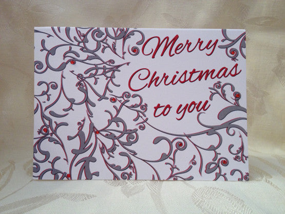 silver and red flourish design decorated with red jewels and a christmas greeting