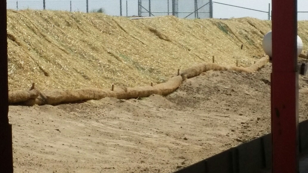 """Straw wattle with 18"""" wood stakes every 10'. Also pictured are straw blankets on the hill slope."""