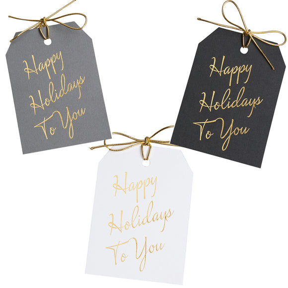 Gold foil Happy Holidays To You gift tags on gray, black, and white linen paper, with metallic gold ties. 3x4