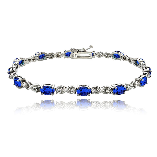 Sterling Silver Created Blue Sapphire 6x4mm Oval Infinity Bracelet with White Topaz Accents