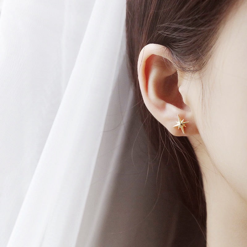 Star gold earring on ear