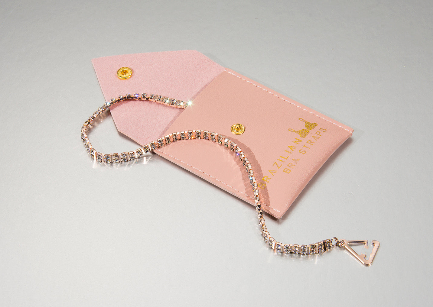 rose gold bra straps on a faux leather pouch