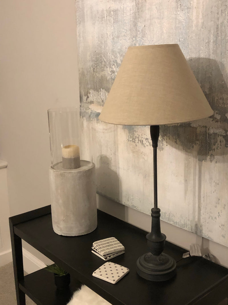 Tall black metal lamp with grey linen shade