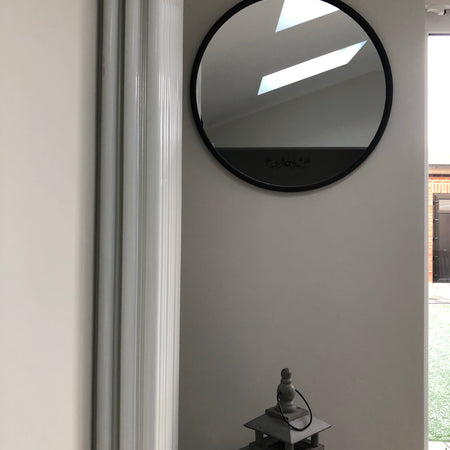 Black round mirror with gold accent and fob detail