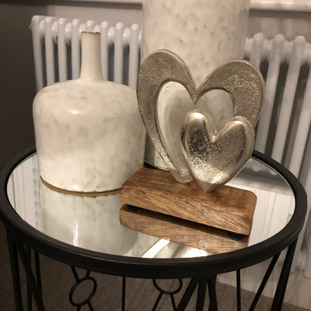 Metal double heart ornament on wooden stand