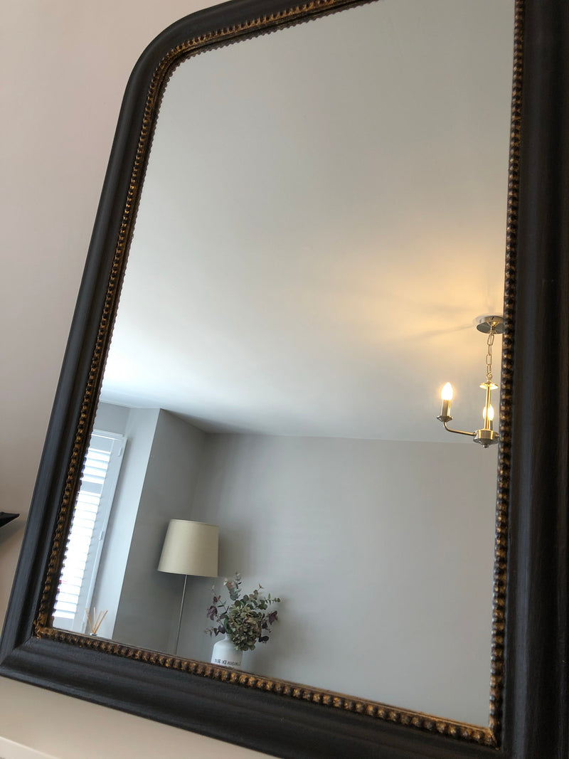 Black and gold mirror with shaped top