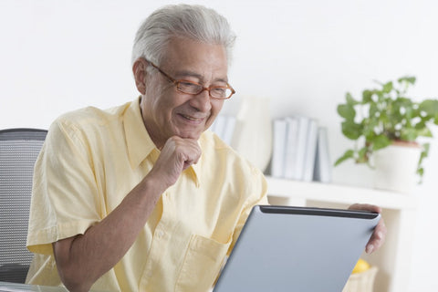 Elderly man happily working on computer