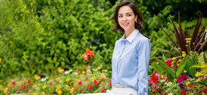 Lady in the garden dressed in blue-and-white striped pattern, white collared non-iron shirt