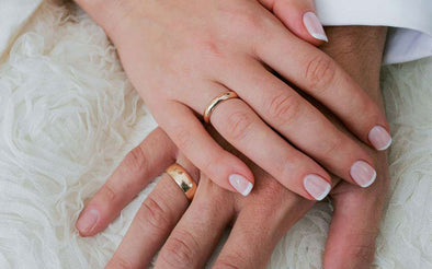 couples wearing gold wedding band