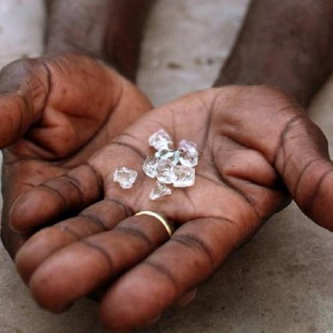 muddy hand of labor holding diamond