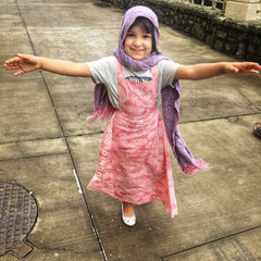Little girl dressed in an adorable organic cotton natural dyed pink pinafore maxi dress smiling and twirling