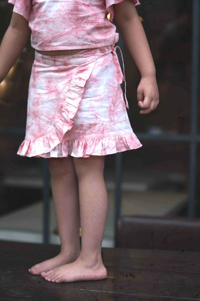 Little girl in pink wrap around skirt made with organic cotton and natural dye.