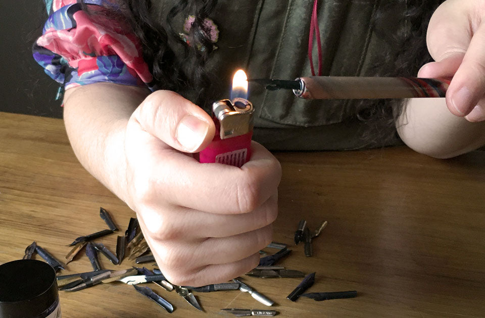 Passing a nib through a flame to remove the coating