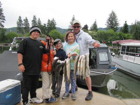 Boat Captain Matt McComb and happy young anglers with a stringer of lake trout at the Jerry Howard Fishing Without Barriers Day on June 15, 2017.  The event was held on the east shore of Flathead Lake with the help of 16 boat captains.