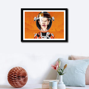 Matt Damon in his Caricature Art Form by Prasad Bhat. Image shows wall decor of the framed art poster of Martian avatar by Matt looking straight forward with his sleek eyes . He is wearing the astronaut's suit and helmet against a predominantly orange background.