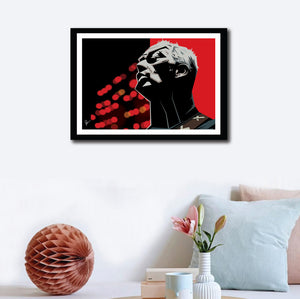 Framed Poster of David Gilmour on a wall decor. Caricature art by Prasad Bhat. Image shows the artist in a performing moment with a angular view of his face. The artwork is predominantly composed with red and black colors.