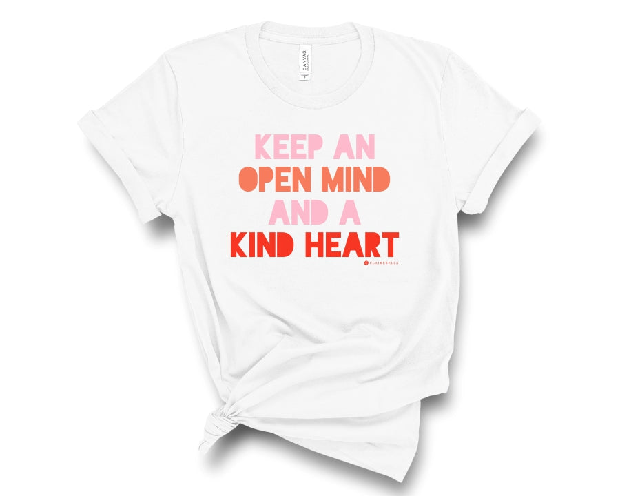 "White, crew neck t-shirt with ""Keep an open mind and a kind heart"" in pink, orange, and red block lettering"