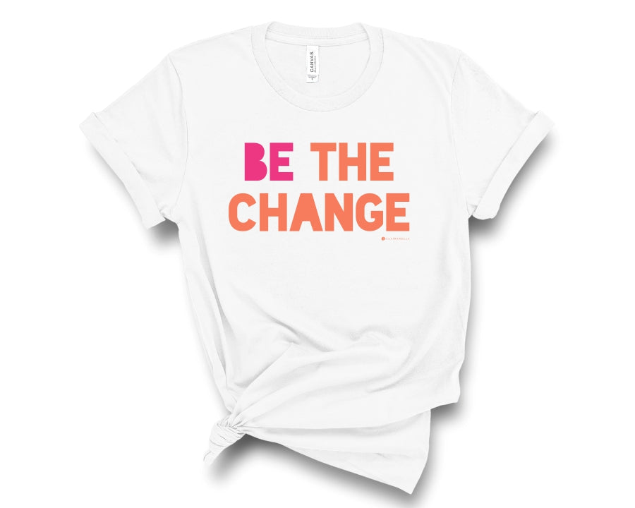 "White, crew neck t-shirt with ""Be the change"" in pink and orange block lettering"