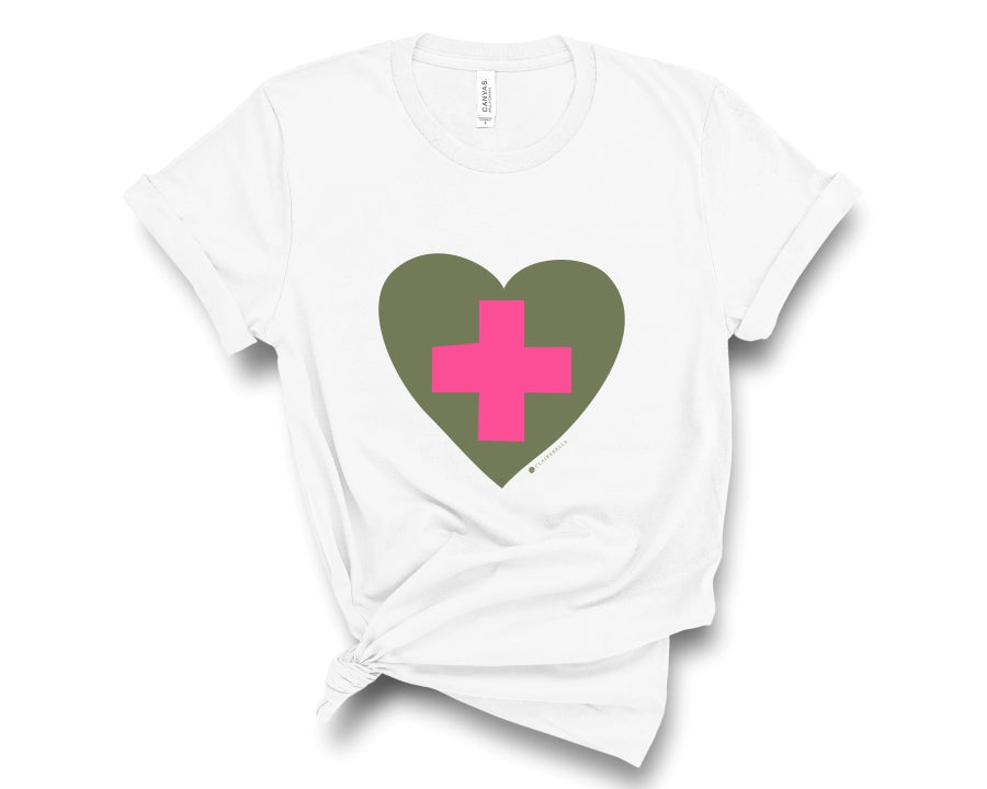 White, crew neck tee shirt with graphic of a pink healthcare cross inside olive green heart
