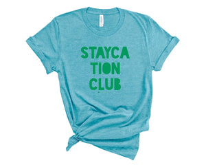 Blue, crew neck t-shirt with Staycation Club in green block lettering.